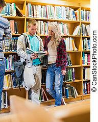 joven, estudiantes, libro de lectura, en, el, biblioteca