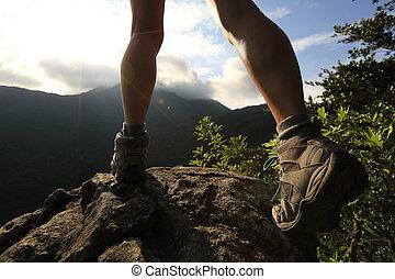 joven, excursionista, piernas, excursionismo, en, pico de la montaña