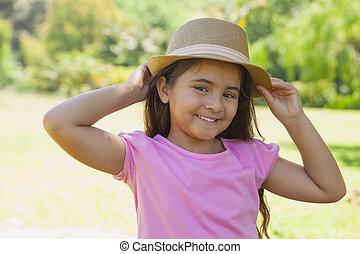 joven, feliz, niña, llevando, sombrero, en el estacionamiento
