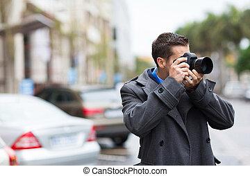 joven, fotógrafo, disparando, fotos, en la lluvia