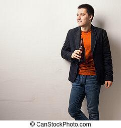 joven, guapo, hombre, bebida, oso, de, botella de vidrio, posición, cerca, pared, en, el, barra