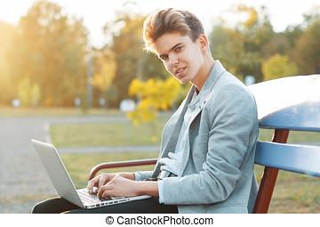joven, guapo, hombre que sienta, en, un, banco, en el parque, en, sunset., asideros, un, cuaderno, en, manos, y, working..