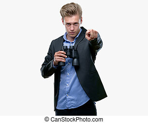 joven, guapo, rubio, hombre, mirar a través de binoculares, señalar, con, dedo, a la cámara, y, a, usted, señal de mano, positivo, y, confiado, gesto, de, el, frente