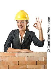 joven, hembra, constructor, cerca, pared ladrillo