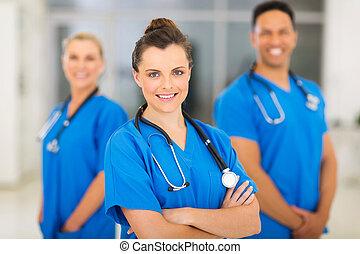 joven, hembra, enfermera, con, colegas, fondo
