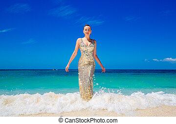 joven, hermoso, niña, en, oro, vestido, en la playa, de, un, tropical, island., vacaciones del verano, concept.