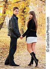 joven, hermoso, pareja, enamorado, manos de valor en cartera, de, otoño, parque