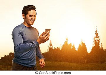 joven, hombre asiático, posición, en, entrenamiento, ropa, utilizar, el suyo, teléfono