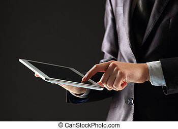 joven, hombre de negocios, trabajando, con, moderno, dispositivos, tableta de digital, pc, en, un, fondo negro