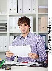 joven, hombre de negocios, valor en cartera instrumentos de crédito, en el escritorio