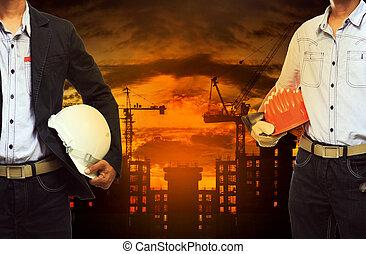 joven, ingeniero, hombre estar de pie, con, casco de seguridad, contra, edificio