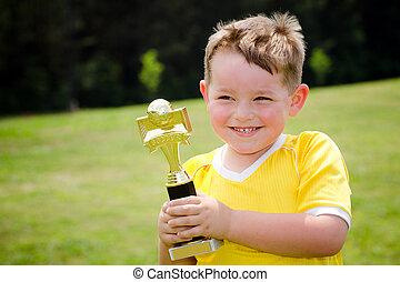 joven, jugador del fútbol, en, uniforme, con, el suyo, nuevo, trofeo