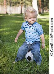 joven, lindo, niño, juego, con, pelota del fútbol, en el estacionamiento