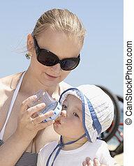 joven, madre, alimentación, ella, hijo, en, el, playa.
