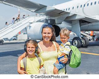 joven, madre, con, dos, niños, delante de, avión
