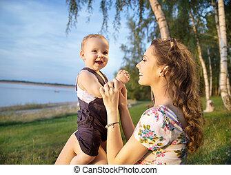 joven, madre, elaboración, ella, bebe riendo