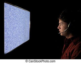joven, mirar fijamente, en, estático, televisión, pantalla de computadora