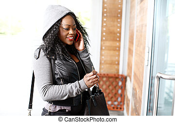 joven, mujer africana, conversación sobre un teléfono móvil
