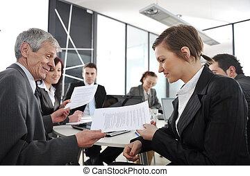 joven, mujer de negocios, en, reunión negocio, en, oficina, con, colegas, en, plano de fondo
