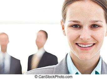 joven, mujer de negocios, posar, delante de, dos, hombres de negocios
