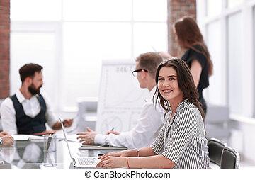 joven, mujer de negocios, sentado, en, escritorio de oficina