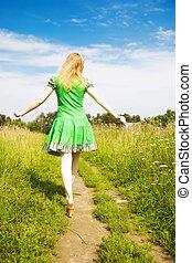 joven, mujer feliz, ambulante, en, un, campo