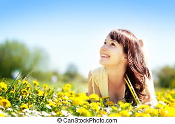 joven, mujer hermosa, yacer césped, lleno, de, flores del...