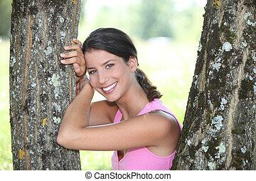joven, mujer sonriente, posar, en, un, parque
