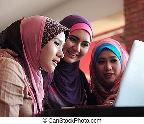 joven, musulmán, mujer, en, dirija bufanda, usar la computadora portátil, en, café, con, amigos