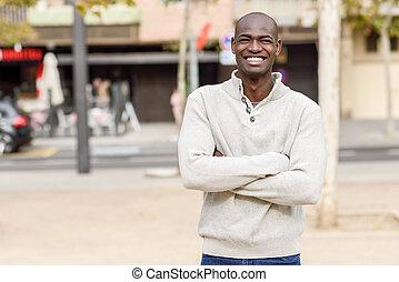 joven negro, con, armamentos cruzaron, sonriente, en, urbano, plano de fondo