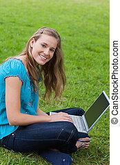 joven, niña sonriente, mirar la cámara, mientras, utilizar, ella, computador portatil