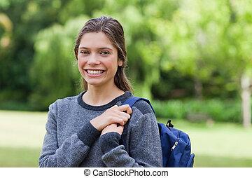 joven, niña sonriente, posición, vertical, en, un, parque