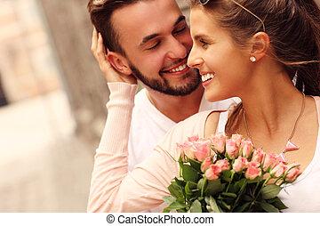 joven, par romántico, con, flores