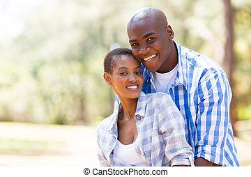 joven, pares americanos africanos, aire libre