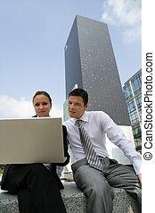 joven, pares del negocio, sentado, con, computador portatil, en, ciudad, centro