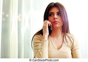 joven, pensativo, mujer que habla teléfono, en casa