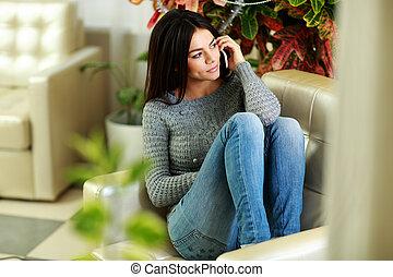 joven, pensativo, mujer que habla teléfono, y, el mirar lejos, en casa