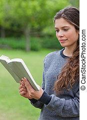 joven, relajado, lectura de la muchacha, un, libro, en, un, parque