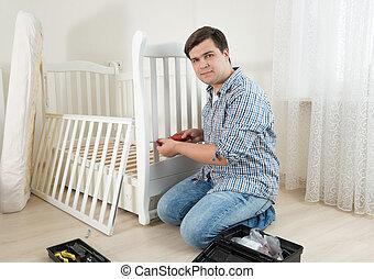 joven, sentar piso, y, reparación, niño, cama