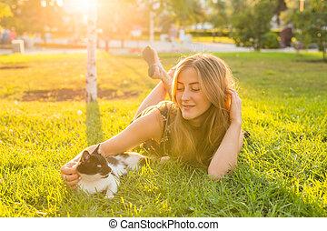 joven, sonreír feliz, mujer, con, gato, en, natural, plano de fondo