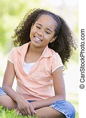 joven, sonriente, niña sentada, aire libre