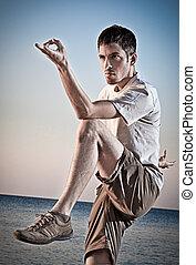 joven, thai-chi, atractivo, elaboración, movimientos, hombre