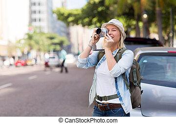 joven, turista que toma foto, en, ciudad