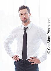 joven, y, successful., confiado, joven, hombre de negocios, en, traje, mantener, armamentos cruzaron, y, sonriente