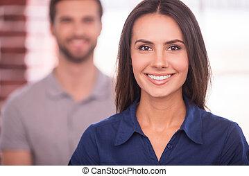 joven, y, successful., hermoso, mujer joven, mirar cámara del juez, y, sonriente, mientras, hombre estar de pie, atrás, ella