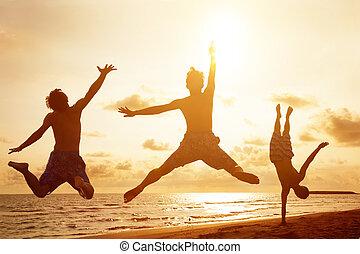 jovens, pular, praia, com, pôr do sol, fundo