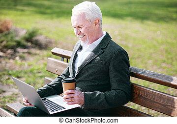 Jovial senior businessman reading report