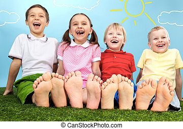 Joy - Group of happy children lying on a green grass