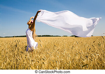 Image of happy woman holding a white fabric in wheat meadow