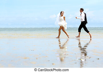 bride and groom playfully at the beach